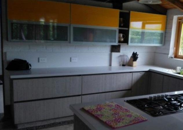 Cocina moderna meson cuarzo blanco y paneles amarillos.